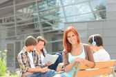 Smiling student girl with friends outside college — Stock Photo