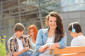 Student girl sitting outside campus with friends — Stok fotoğraf
