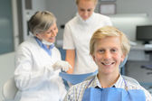 Teenage patient, dentist woman with dental assistant — Stock Photo