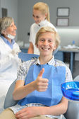 Teenager patient thumbup at dental surgery dentist — Photo