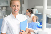 Dental assistant smiling dentist with patient — Stock Photo