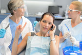 Busy businesswoman at dental surgery on phone — Stock Photo