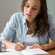 Teenage girl writing notes — Stockfoto