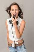 Teenage girl singing with microphone — Stock Photo