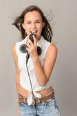 Teenage girl singing with microphone — Stock Photo