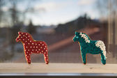 Gingerbread painted horses at wide window frame — Stock Photo