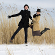Royalty-Free Stock Photo: Man and woman jump on lake beach