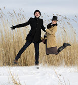 Man and woman jump on lake beach — Stock Photo