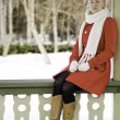 Foto Stock: Womin red coat sit at boundary