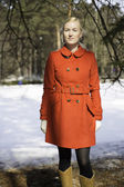 Young woman in red coat under spruce — Stock Photo