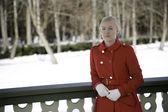 テラスで赤いコートで若い女性 — ストック写真