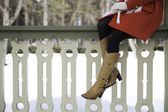 Woman legs with boots at terrace boundary — Stock Photo