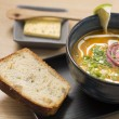 Ceramic bowl with delicious soup and bread — Stock Photo