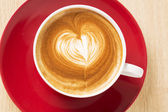 Zoomed cup of coffee with foam heart — Stock Photo