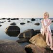 Woman in white dress sit on stone — Stock Photo