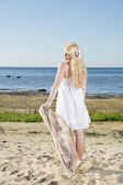 Young woman walking with scarf at beach — Stock Photo