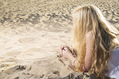 Woman in dress draw hearts on sand — Stock Photo
