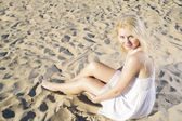 Woman in white dress posing on sand — Stock Photo