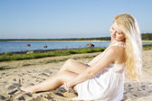 Woman in white dress indulgence on sand — Stock Photo