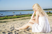 Woman in white dress indulgence on beach — Stock Photo