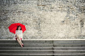 Woman sit with open umbrella at steps — Stock Photo