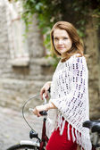 Woman in red hold tightly after bicycle — Stock Photo