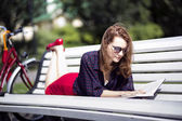 Woman lying on bench and read book — Stock Photo