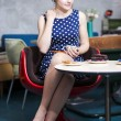 Stock Photo: Womin white spotted dress hold cup