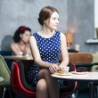 Stock Photo: Zoomed womin spotted dress in cafe