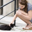 Stock Photo: Womin checkered dress fondle street cat