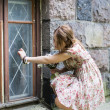 Woman in dress knocking on window glass — Stock Photo