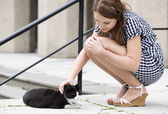 Woman in checkered dress fondle street cat — Stock Photo