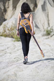 Woman with yellow guitar over shoulder — Stock Photo