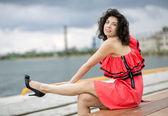Woman in dress stroking leg — Stock Photo