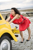 Woman in red dress pushing lightly car — Stock Photo