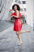 Woman in red dress mimicking run — Stock Photo