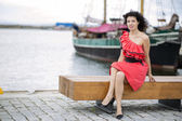 Woman in red dress posing at harbor — Stock Photo