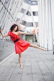 Woman in red dress posing on leg — Stock Photo