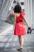 Woman in red dress stretches feets — Stock Photo