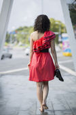 Woman in red dress walking barefoot — Stock Photo