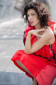 Woman in red dress squatting at square — Stock Photo