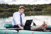 Dressed man in boat and reading — Stock Photo