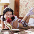 Stock Photo: Womin schoolgirl dress chews apple