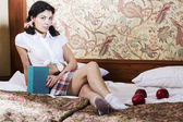 Woman in schoolgirl dress on bed — Stock Photo