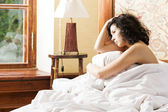 Woman under soft cover scratching her head — Stock Photo