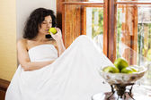 Woman smells green apple on wooden sill — Stock Photo
