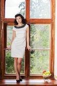 Woman in nice dress stand on sill — Stock Photo