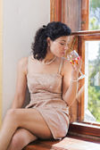 Woman sit on sill and smells wine — Stock Photo