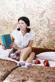 Woman in schoolgirl dress with mysterious book — Stock Photo