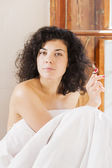 Pretty woman play with hair between bedclothes — Stock Photo
